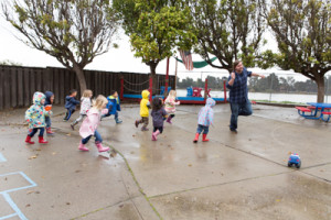 Teacher skipping with kids in the rain
