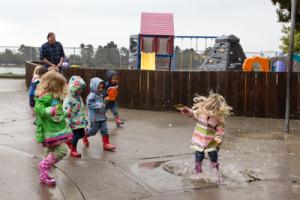 toddler splashing in puddle
