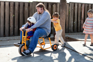 Teacher on tricycle with kids